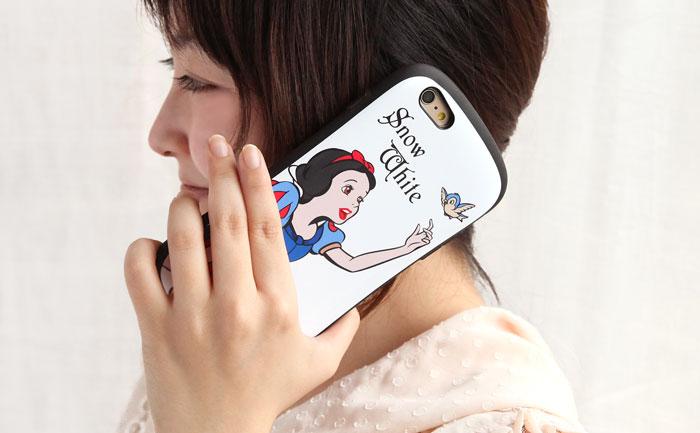女性が白雪姫のケースを持って電話をしている。