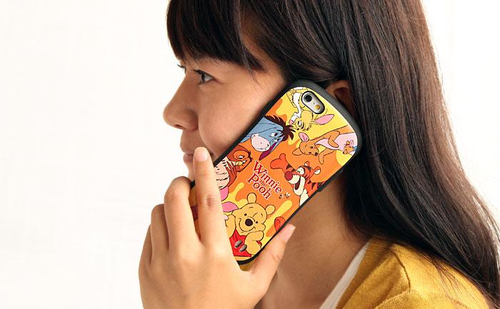 女性がプーさんのケースを持って電話をしている画像。