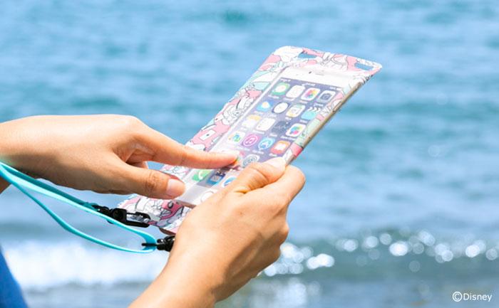 海でアリスのケースでiPhoneを触っている。