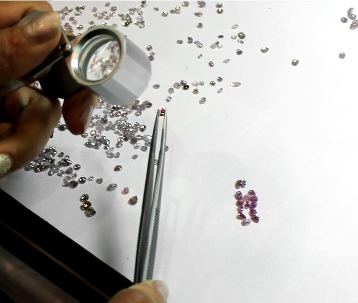 アーガイル産天然ピンクダイヤモンドのルースを選り分けているバイヤー