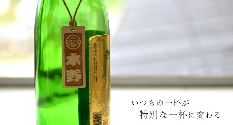 窓辺に置いてある緑色の一升瓶にかけられたボトルネックの写真