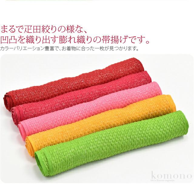 華やかなふくれ織りの振袖用正絹帯揚げです。まるで疋田絞りの様な、凹凸を織り出す膨れ織りの帯揚げです。カラーバリエーション豊富で、お着物に合った一枚が見つかります。立体感があり振袖に相応しいボリューム。緯糸に銀糸を織り込んだ銀通し生地を使用し、きらきらと華やかに輝きます。小物一つ一つにこだわり、とっておきの着物で晴れの日をお祝いしてください。