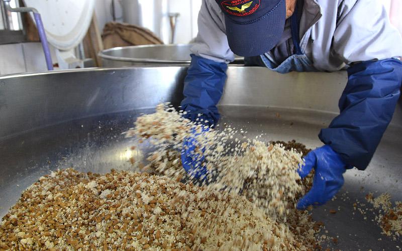 巨大な釜の中で米麹を大豆を混ぜ合わせる。