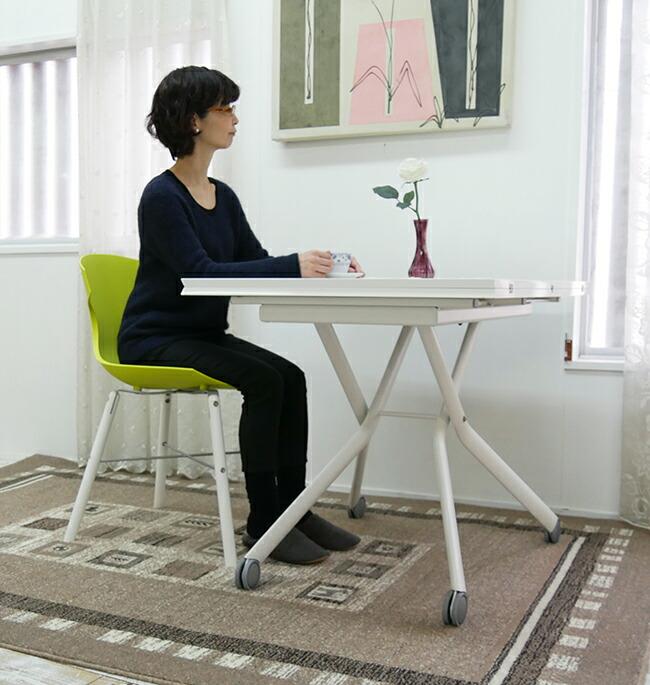 白いリフティングテーブルに合う、個性的な緑色のデザイナーズチェア