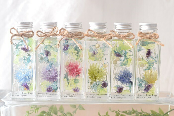 ハーバリウム いつもお世話になっている方に…  感謝の気持ちを込めて、ハーバリウムの贈り物はいかがですか? ハーバリウムは、おしゃれなインテリアアクセサリーとして注目されています。 専用のオイルに浸すことでお花や植物の鮮やかな色とみずみずしい美しさが 長く保たれます。 アトリエブルージュオリジナルのデザインです。 デザイナーが1つ1つ心を込めてお作りいたします。  出来上がりの完成品で、そのままお渡しいただけます。 クリアケースにリボンとシールのかわいいギフトラッピングでお届けします。 また、メッセージカード、持ち運び袋も無料でお付けできます。  持ち運びや配送にも便利。  お手入れ不要のハーバリウムは、そのまま飾っていただけて、きっとお母さまに 喜んでいただけるでしょう。