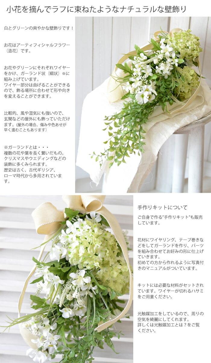 """小花を摘んでラフに束ねたようなナチュラルな壁飾り 白とグリーンの爽やかな壁飾りです!  お花はアーティフィシャルフラワー(造花)です。  お花やグリーンにそれぞれワイヤーをかけ、ガーランド状(綱状)※に組み上げています。 ワイヤー部分は曲げることができるので、飾る場所に合わせて形や向きを変えることができます。  比較的、風や湿気にも強いので、玄関などの屋外にも飾っていただけます。 (屋外の場合、傷みや色あせが早く進むこともあります)  ※ガーランドとは・・・ 複数の花や葉を長く繋いだもの。 クリスマスやウエディングなどの装飾に多くみられます。 歴史は古く、古代ギリシア、ローマ時代から多用されています。  手作りキットについて ご自身で作る""""手作りキット""""も販売しています。  花材にワイヤリング、テープ巻きなどをしてガーランドを作り、パーツを組み合わせてお好みの形に仕上げ ていきます。 初めての方から作れるように写真付きのマニュアルがついています。  キットには必要な材料がセットされています。ワイヤーが切れるハサミをご用意ください。  光触媒加工をしているので、周りの空気を綺麗にしてくれます。 詳しくは光触媒加工とは?をご覧ください。"""