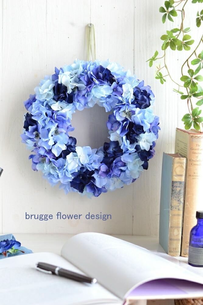 こちらの商品はアートフラワー(造花)の完成品です。 アジサイだけのシンプルなリース4種類のアジサイをミックスすることで、よりニュアンスのある深い色合いに仕上がりました。 スタイリッシュな空間を演出します。 アーティフィシャルフラワー(造花)は、お手入れ不要!<br><br> 湿気や風に強く、簡単なお手入れで半永久的に楽しめます。 直径約25~26cm。玄関のドアにかけても十分存在感のある大きさです。 テーブルリースとしてもお使いいただけます。 *アーティフィシャルフラワーとは・・・布でできた造花。アートフラワー、シルクフラワーとも呼ばれています。 *光触媒加工をしてお届けします。