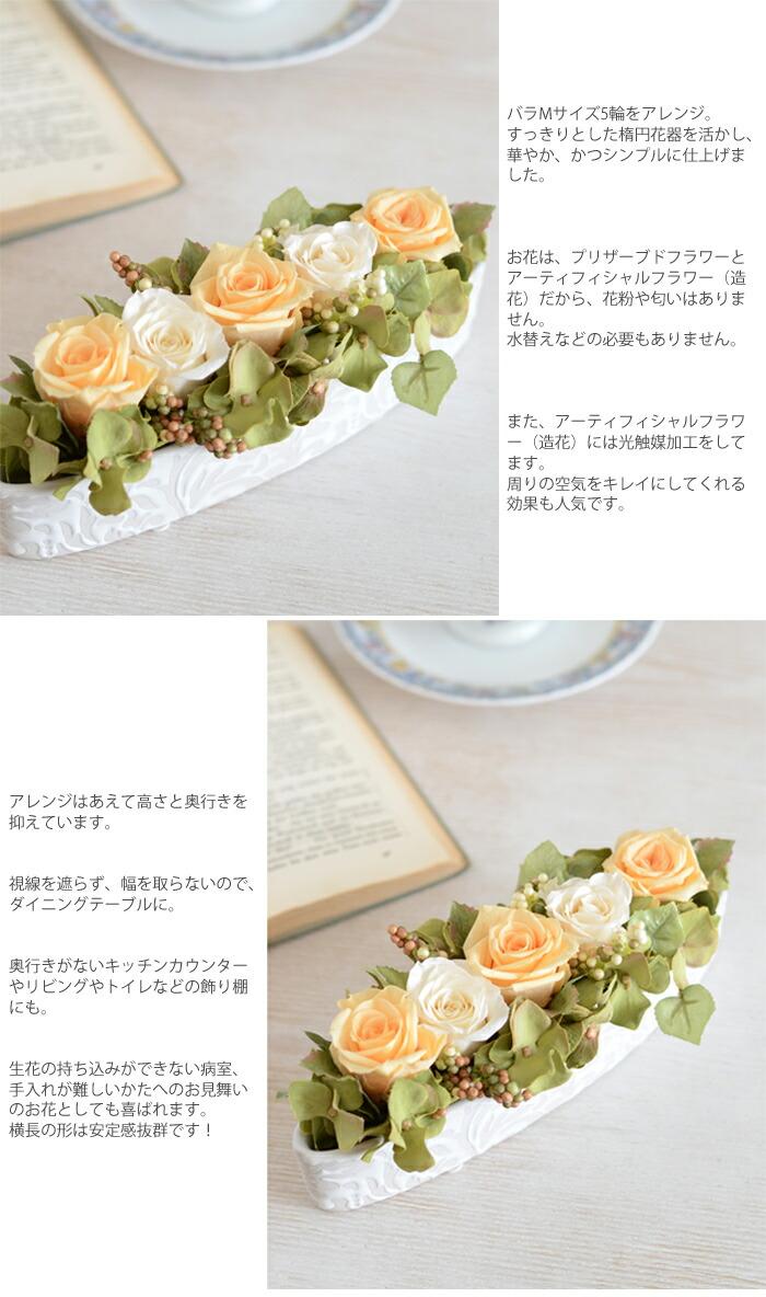 バラMサイズ5輪をアレンジ。 すっきりとした楕円花器を活かし、華やか、かつシンプルに仕上げました。  お花は、プリザーブドフラワーとアーティフィシャルフラワー(造花)だから、花粉や匂いはありません。 水替えなどの必要もありません。  また、アーティフィシャルフラワー(造花)には光触媒加工をしてます。 周りの空気をキレイにしてくれる効果も人気です。  アレンジはあえて高さと奥行きを抑えています。  視線を遮らず、幅を取らないので、ダイニングテーブルに。  奥行きがないキッチンカウンターやリビングやトイレなどの飾り棚にも。  生花の持ち込みができない病室、手入れが難しいかたへのお見舞いのお花としても喜ばれます。 横長の形は安定感抜群です!