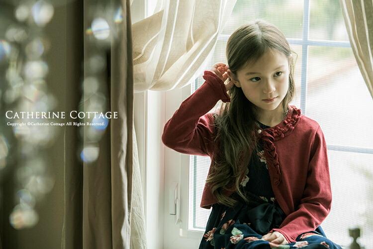 赤い長袖ニットボレロを着た女の子