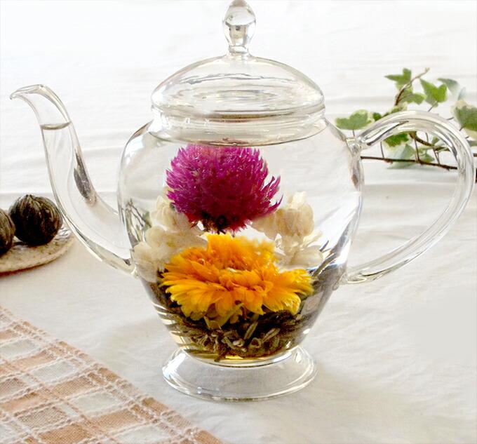 ガラス製ポットの中のピンク、黄色、白の花が入った工芸茶