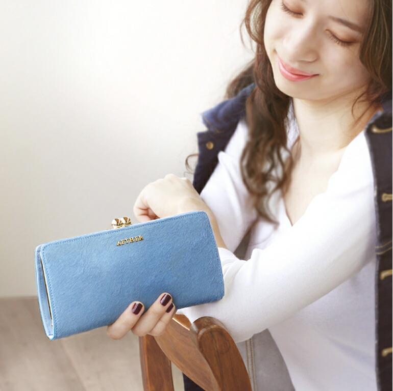 女性が青い財布を持っている画像