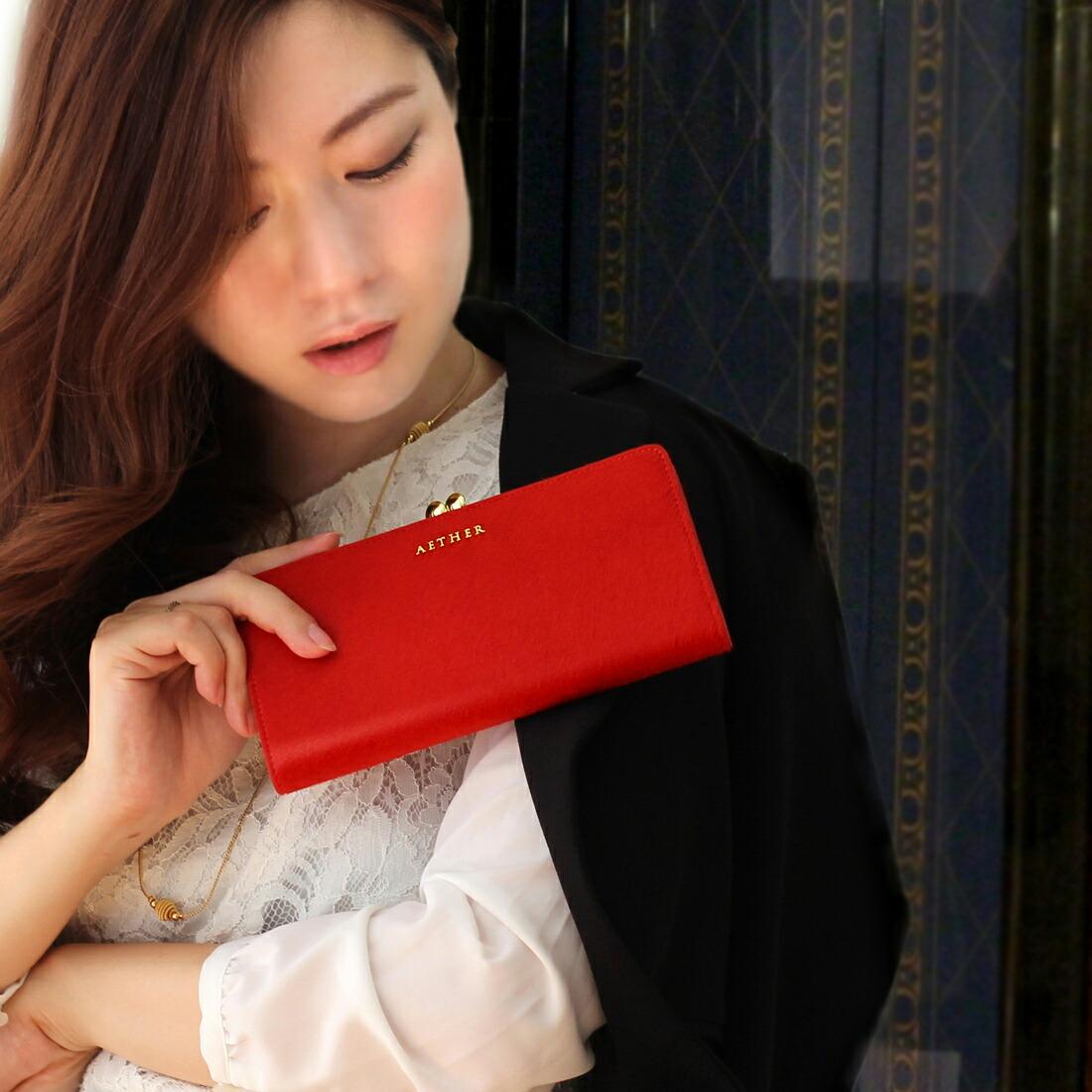 赤いがま口財布を持っている画像