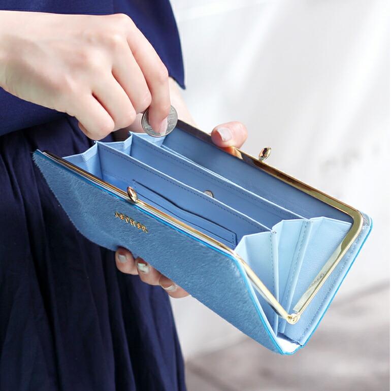 ブルーのがま口財布を開いて小銭を出す画像