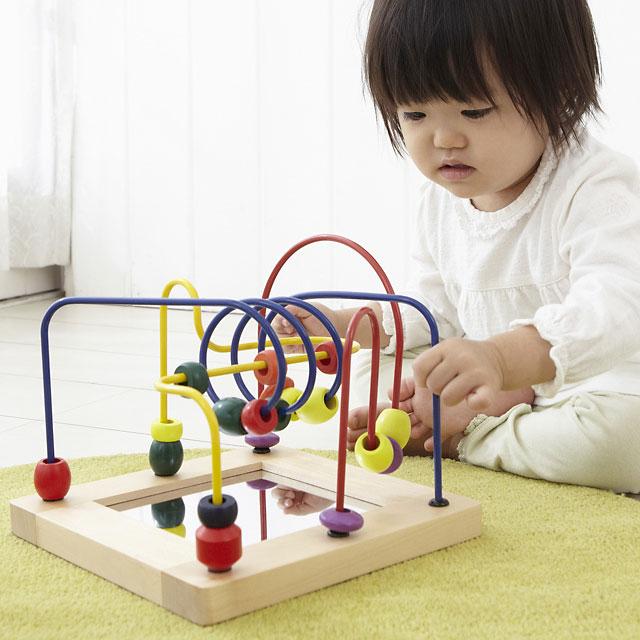木のおもちゃビーズコースターで遊ぶ子ども