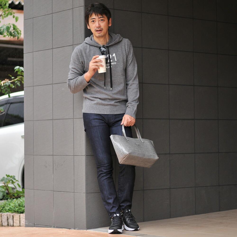 フェリージのミニバッグを手に持つ男性モデル