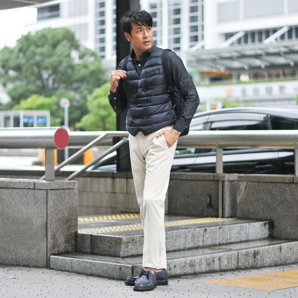 オフホワイトのコーデュロイパンツを履いた男性モデル