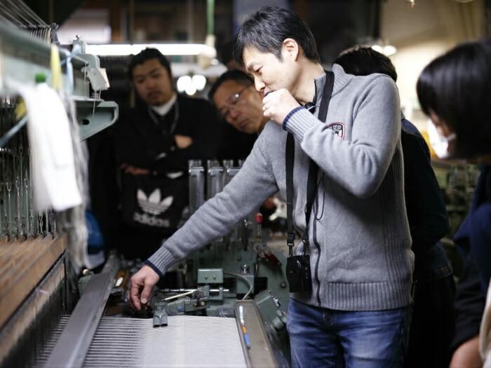 工場を開放して職人自ら織機の説明をする様子