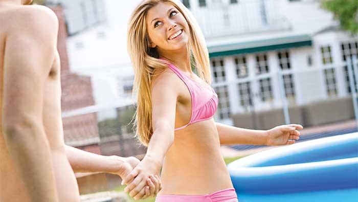 プールの前で男性と手をつなぐ笑顔の金髪の女性