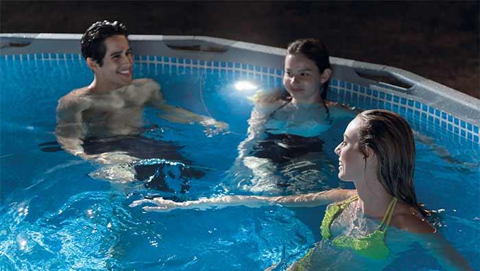 夜にプールの中で遊ぶ男性と女性達