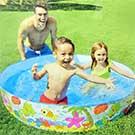 キッズプールで水遊びをする子供達と見守る父親