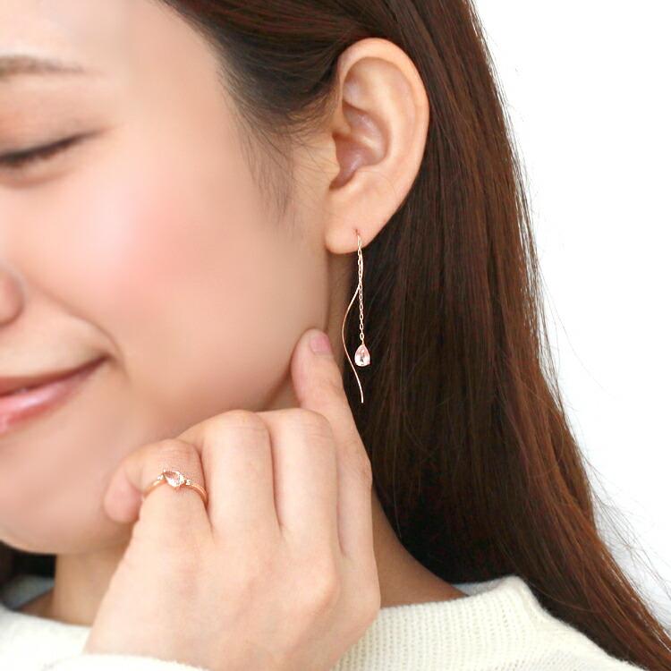 桜モチーフのアメリカンピアスと指輪をつけたモデルの画像