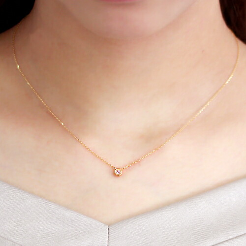 ピンクダイヤモンドの18金ネックレスを装着している手