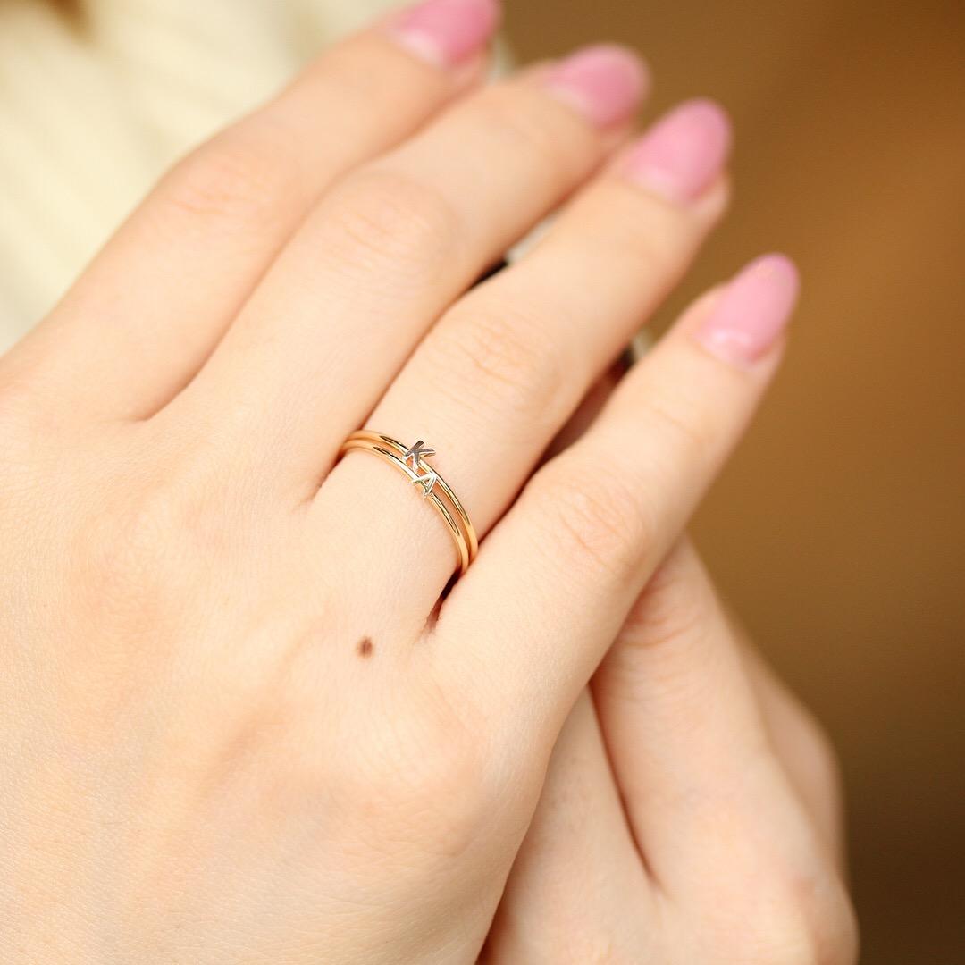 イニシャルモチーフの指輪をつけたモデルの手もと
