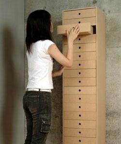 写真はA4書類用引き出し収納棚・21段タイプ(DRW-A4-21)。モデルの身長は160cmです。引出しはA4サイズの紙がぴったり入る大きさです。