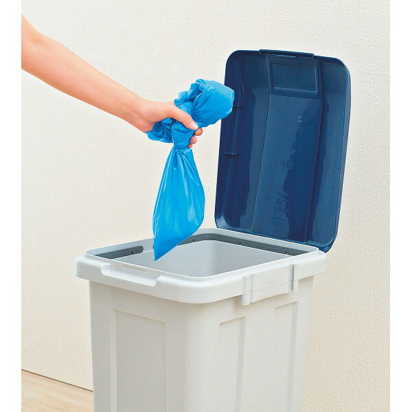汚物袋をゴミ箱に捨てる