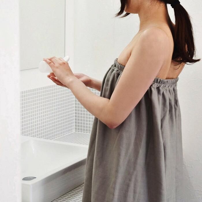 ラップタオルを巻き鏡の前に立つ女性