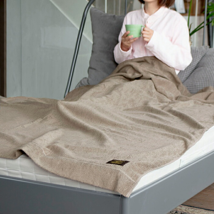 ベッドに入りマグカップを持ってフローズンタオルケットをかける女性