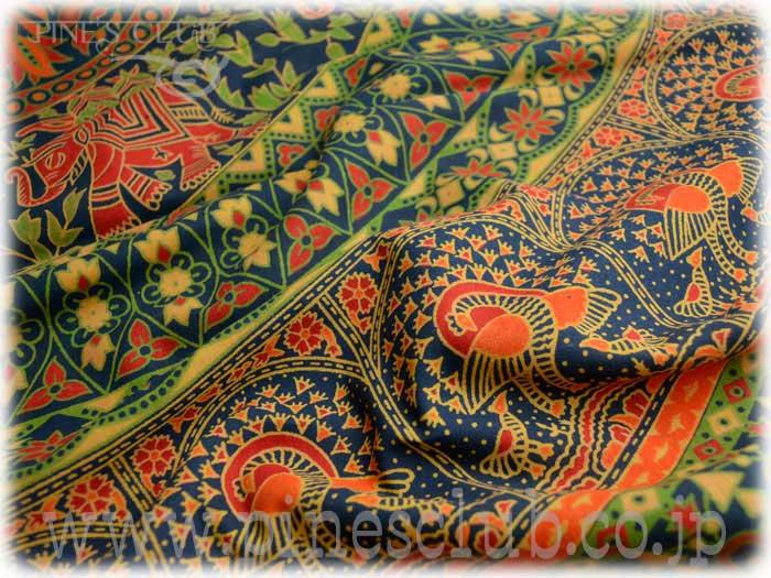ダイナミックなデザインの大きな布です。ベッドカバーのダブルサイズの大きさです。紺地に緑色基調の柄と象、孔雀、鳥で大きな円を描いています。