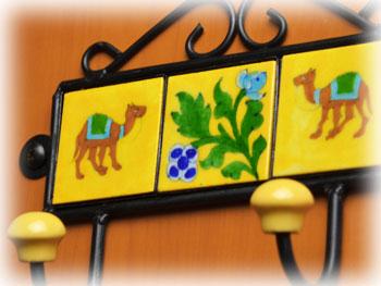 インドの工芸品・ジャイプール焼の陶板を使用した壁掛けフックです。黄色の正方形タイル三枚にラクダと花がそれぞれ描かれています。