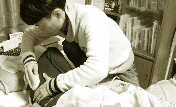 後藤洋が父に温熱施術をしているところ
