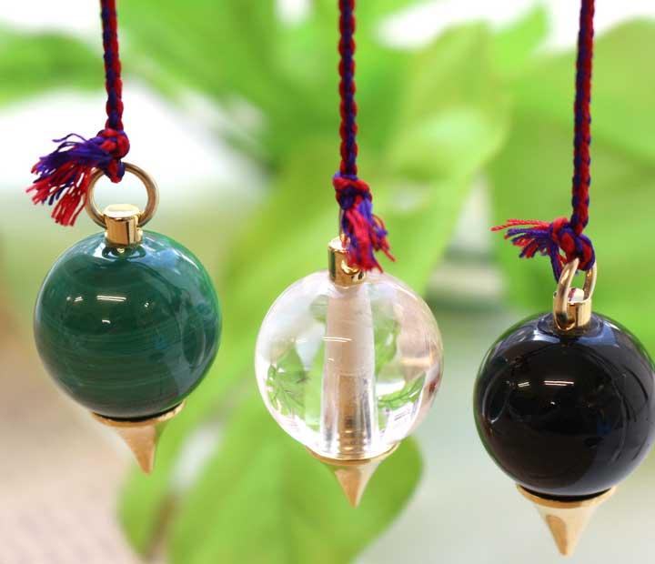 ヒマラヤ水晶・マラカイト・黒水晶のペンデュラム3点セットを紐で吊り下げたイメージ