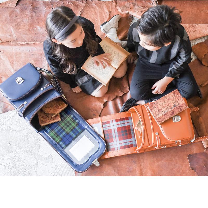 男の子と女の子がカンゴールのランドセルを広げて本を詰め込んでいる風景