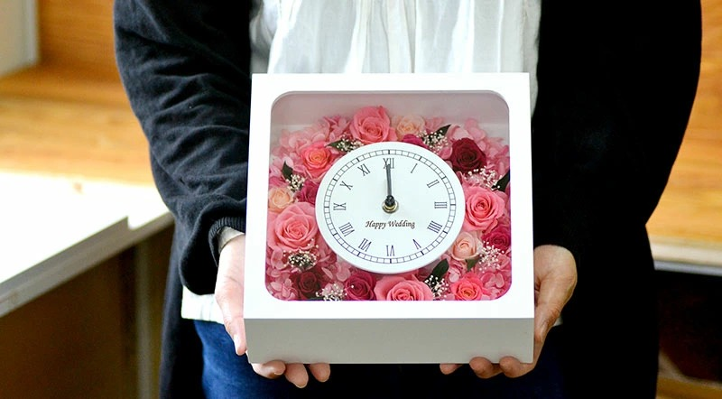 女性が花時計のフルールピンクタイプを抱えている写真