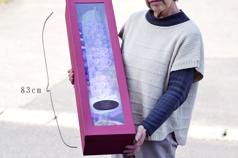 小柄な女性が77輪ローズ花束を抱えているときのイメージ画像