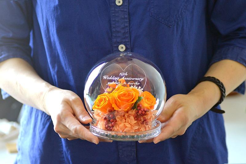 成人女性がROSAオレンジを抱えている写真