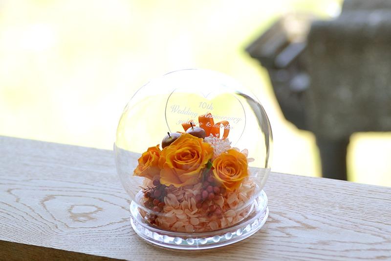 窓辺にドーム型ロサオレンジを飾っている写真