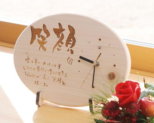 作家文字で描かれた味わいのある大きな笑顔という文字と、笑顔にちなんだポエムが刻まれた木製ヒノキ時計