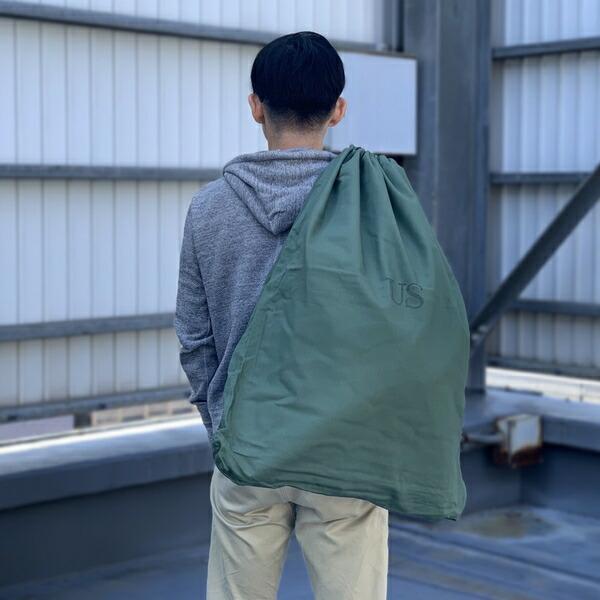550529767411 使い込むほどに味わいが増すミリタリーを代表するファブリックであるコットンサテンを使用した大型の巾着袋。 USのスタンプがいい感じで、バッグや荷物の収納袋として  ...